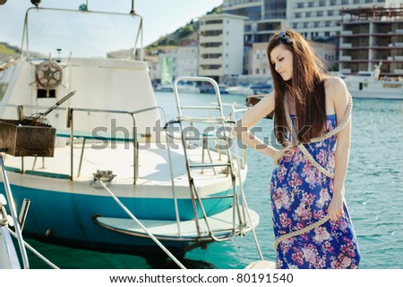 attractive girl on the dock with boat - stock photo