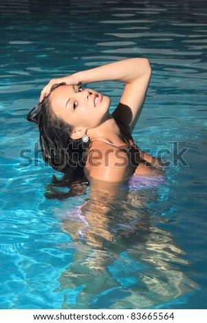 Attractive girl posing in swimming pool at night