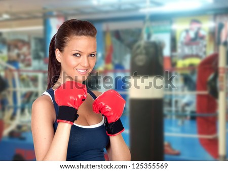 Attractive girl practicing boxing in the gym - stock photo