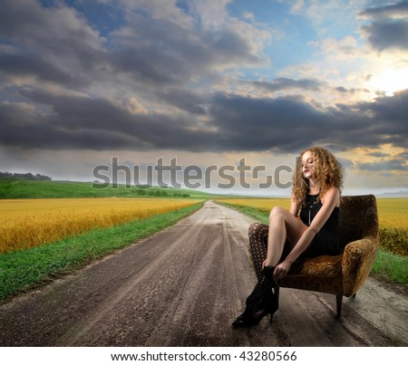 attractive girl seated in armchair in the countryside - stock photo