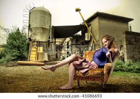 attractive girl seated on armchair with farm in the background - stock photo