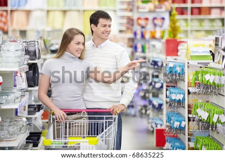 Attractive girl shows a man in the direction of the store - stock photo