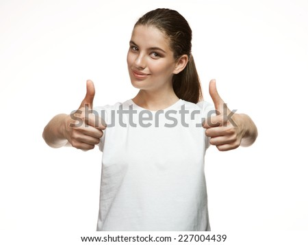 Attractive girl shows thumb up gesture / Gorgeous girl in plain white T-shirt. Mixed race Latina Caucasian young woman gesticulating - isolated on white background.  - stock photo