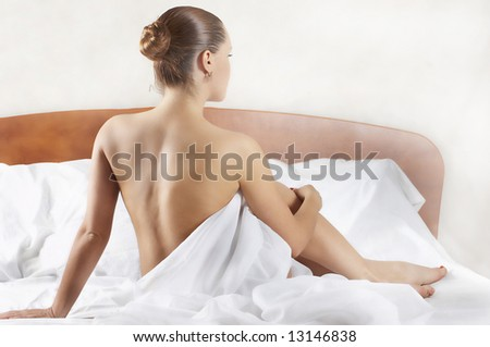 attractive girl sits on beds (type behind) - stock photo