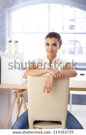 Attractive girl sitting conversely on chair on bright office. - stock photo
