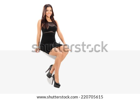 Attractive girl sitting on a blank panel isolated on white background - stock photo