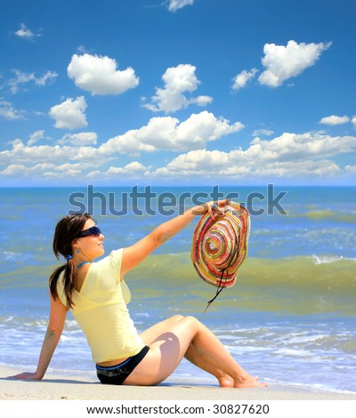 Attractive girl sitting on white sandy beach in the sun - stock photo