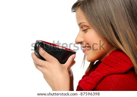 attractive girl smells her hot soup in winter while wearing a festive coloured cardigan - stock photo