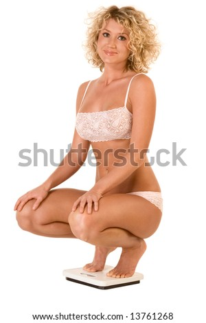 Attractive girl squatting on bathroom scales, checking weight - stock photo