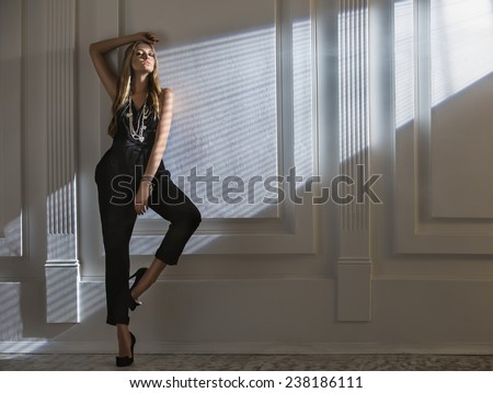 Attractive girl stands raising his hands with eyes closed in the rays of light passing through the jalousie. Fashion shooting. - stock photo