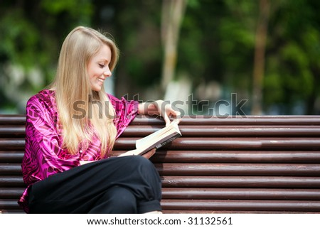 Attractive girl student reading book in summer park. - stock photo