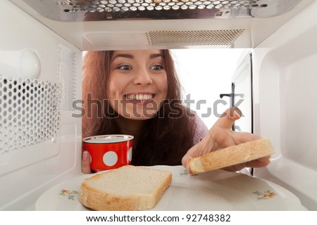 Attractive girl takes tost from a microwave - stock photo