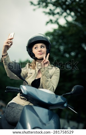 Attractive girl taking selfie while sitting on her scooter - stock photo