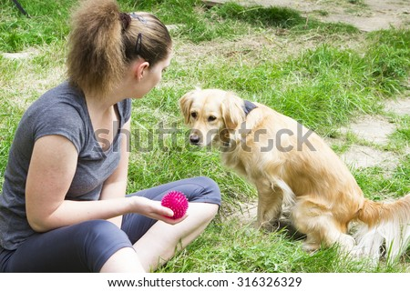 Attractive girl throwing ball to retriever dog while playing - stock photo