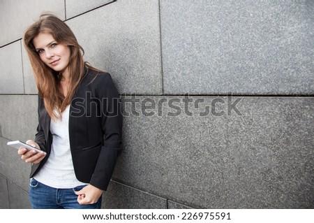 Attractive girl using her smartphone - stock photo