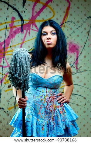 attractive girl with a mop in blue dress on background