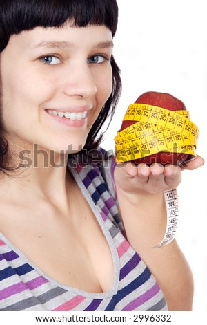 attractive girl with apple and tape measure in the hand a over white background