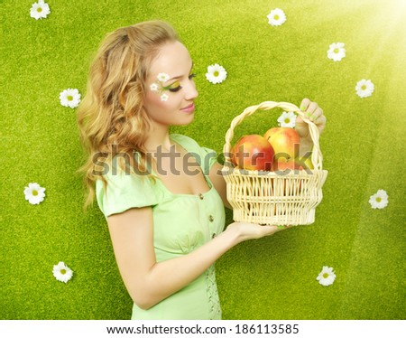 Attractive girl with basket of apples on green background