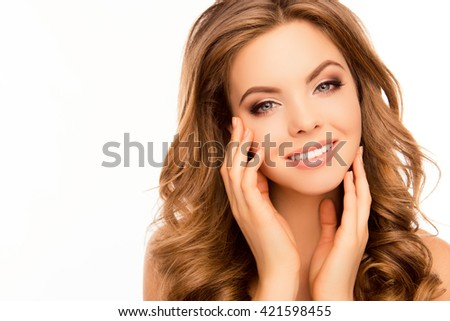 Attractive girl with beaming smile and curly hairstyle touching face - stock photo