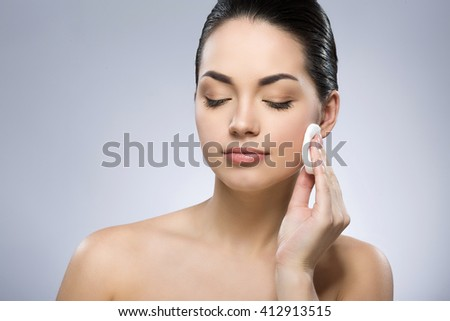 Attractive girl with black fixed hair behind, closed eyes and naked shoulders, cleaning face with cotton pad at gray studio background, portrait, close up. - stock photo