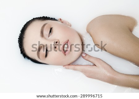 Attractive girl with closed eyes takes a milk bath, touching her face. Perfect skin, nude makeup, romantic atmosphere, beauty cosmetic salon and spa treatment for woman's skin.  - stock photo