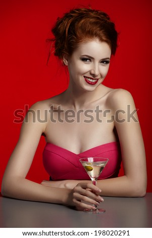 Attractive girl with cocktail, red background, smile. - stock photo