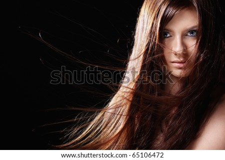 Attractive girl with developing hair on a black background - stock photo