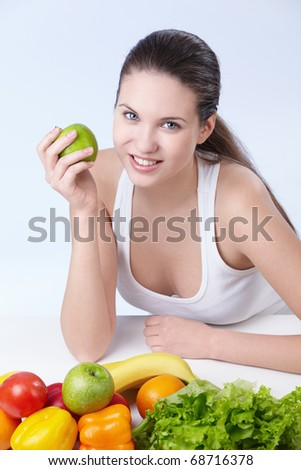 Attractive girl with fruits and vegetables on white background - stock photo