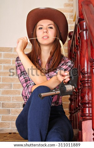 Attractive girl with gun in cowboy hat on staircase in hallway - stock photo