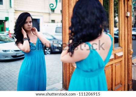 Attractive girl with his reflection in the mirror - stock photo