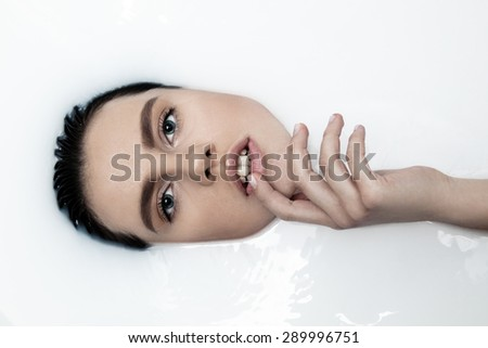 Attractive girl with open eyes takes a milk bath, touching her face. Perfect skin, nude makeup, romantic atmosphere, beauty cosmetic salon and spa treatment for woman's skin.  - stock photo