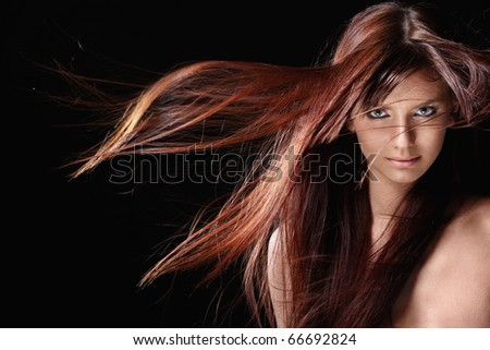 Attractive girl with red hair on a black background - stock photo