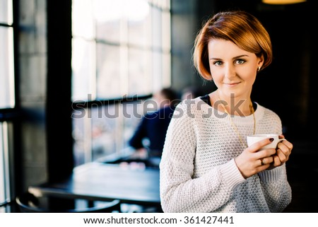 Attractive girl with red short hair wearing in white sweater alone in cafe with chainlet on her neck, holding a cup of coffee, wearing  dark red manicure, smiling, big windows at background.  - stock photo