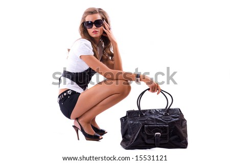 Attractive girl with sexy dress and big fashion bag sitting on the floor. Isolated on white - stock photo