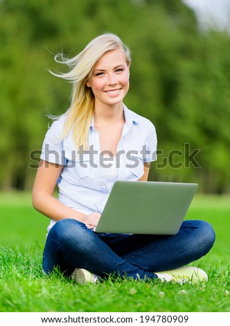 Attractive girl with silver laptop sitting on the grass in the summer park