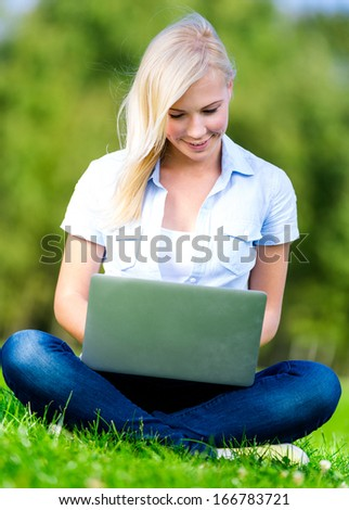 Attractive girl with silver laptop sitting on the green grass in the summer park
