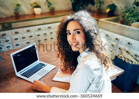 Attractive girl working in a cafe with a laptop during lunch. young business woman searching for information on the Internet and makes notes in a notebook - stock photo