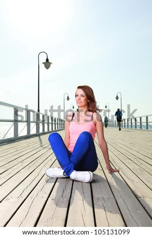 Attractive girl Young woman on pier Sits Crossed Legged Relaxing Old Wooden Pier