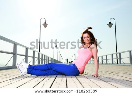 Attractive girl Young woman on pier Sits Relaxing Old Wooden Pier - stock photo