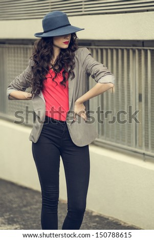 Attractive glamorous brunette wearing stylish clothes posing outside on a cloudy day - stock photo