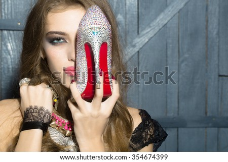 Attractive glamour young fashionable girl with long curly hair bright makeup and costume jewellery of necklace rings and earrings holding diamond shoe with red sole on wooden background, horizontal - stock photo