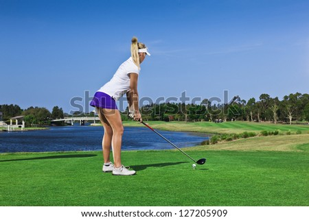 Attractive golfer girl on golf course with driver - stock photo