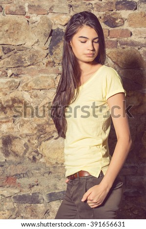 Attractive gorgeous female with long hair posing outside while holding her hand in her pocket - stock photo