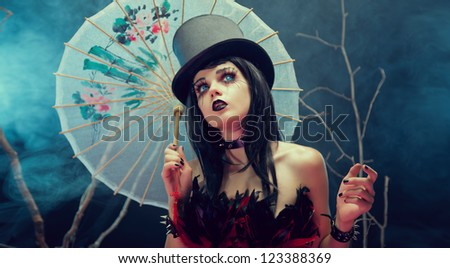 Attractive gothic girl in top hat with Chinese umbrella looking up, studio shot with fog and branches - stock photo