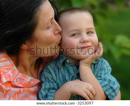 Attractive grandmother giving her young grandson a kiss on the cheek; selective focus on the boy - stock photo