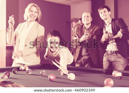 Attractive group of friends playing billiards and smiling in billiard club. Focus on the young woman