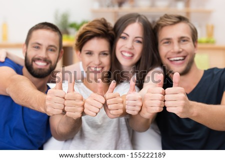 Attractive group of happy young men and women giving a thumbs up gesture of approval and success with focus to their hands - stock photo