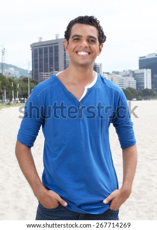 Attractive guy in a blue shirt with cityscape in the background - stock photo