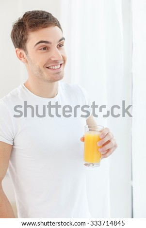 Attractive guy is drinking orange juice in the morning. He is standing near the window and smiling - stock photo