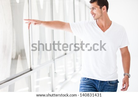 Attractive Guy pointing out the window as he is walking through a Penthouse - stock photo